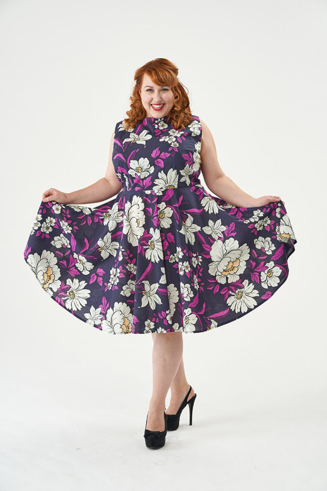 Hildy wearing a floral Betty Dress, holding the edges of the skirt outwards to show it off - Sew Over It sewing patterns