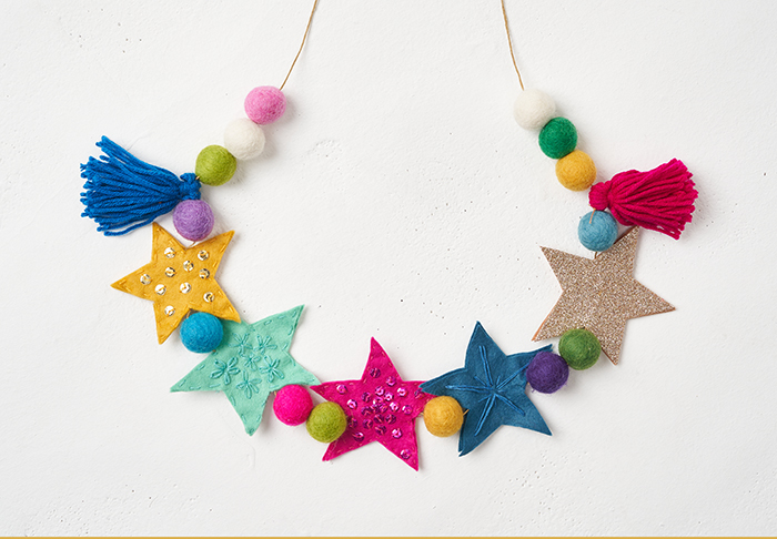 Hand sewn Christmas garland made from brightly coloured felt stars and assorted pompoms