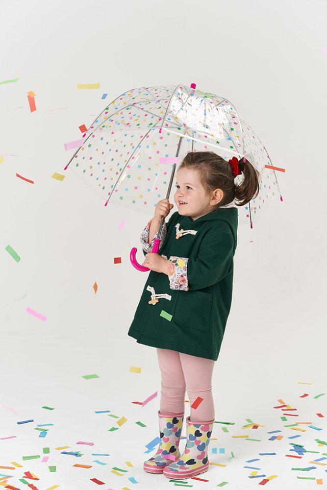 Jasmine holding a transparent umbrella while wearing the Poppy & Jazz Walnut Duffle Coat, surrounded by giant multi-coloured confetti!