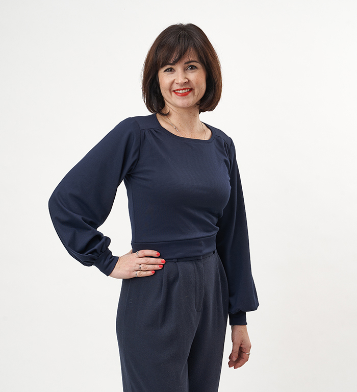 Lisa wearing a navy Roxy Jumper, with her hand on her hip and smiling