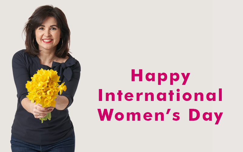 Lisa wearing the Audrey Top and holding a bunch of bright yellow daffodils for International Women's Day 2021